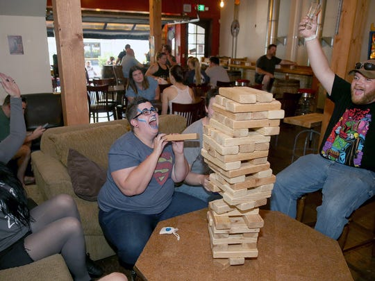From left, Katelyn Ziegenhagen of Port Orchard, Nic Shakley of Silverdale, and Zach Siltanen of Port Orchard celebrate Shakley's, Jenga move at Dog Days Brewing during the 2018 Nerd Crawl in downtown Bremerton on July 26.