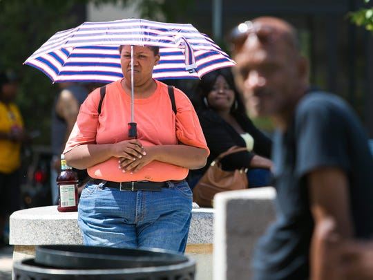 """It's hot as hell"", says Nadiyyah Ennals, 32, of New Castle as she shields herself from the hot sun with an umbrella waiting for her bus to arrive at Rodney Square Monday. This is the 10th record hot month in a row on earth, according to NASA."