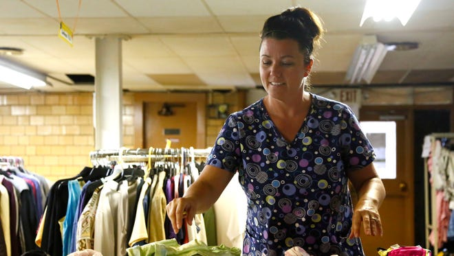 Christina Richie, a volunteer at Reaching Out, folds clothes in the basement of Armor Bearers Ministries at 200 Ashland Road in Mansfield. The non-profit has recently been asked to vacate the property from the pastor of Armor Bearer Ministries.
