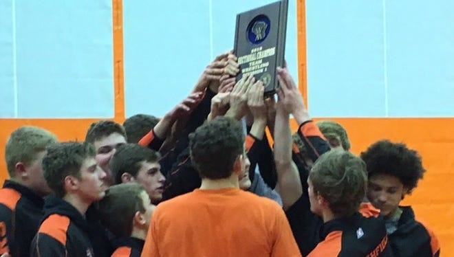 Members of the Marshfield wrestling team raise a championship plaque after beating Hudson in a WIAA Division 1 team sectional on Tuesday.