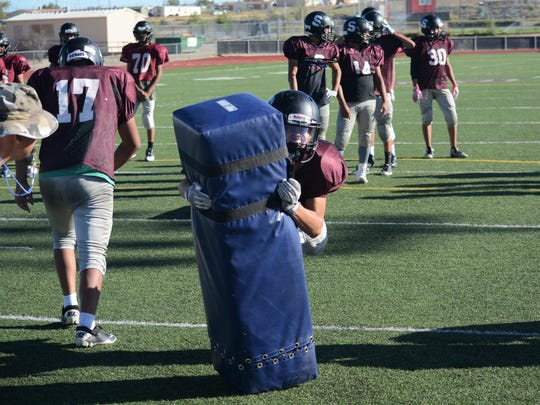 Shiprock's Tyrell Bruce wraps his arms arounda dummy and lunges forward while bringing it down during tackling drills at Wednesday's practice.