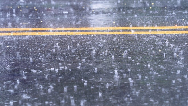 Photo illustration of rain falling on a road