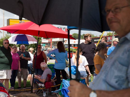 People wait in line to buy solar viewing glasses for