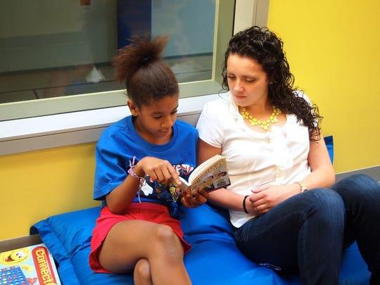 Volunteer Maura Kalil listens to a summer camper reading in Burlington