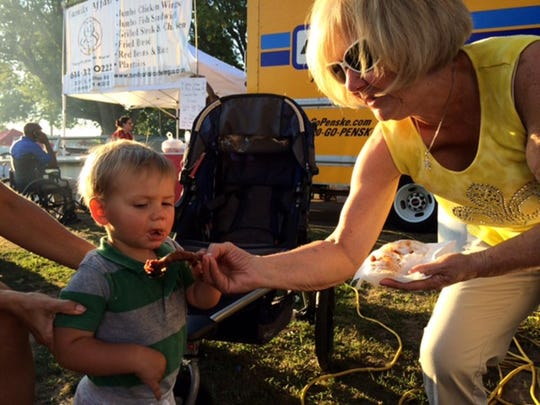 A youngster tries ribs at last year's Rib Fest at the Muskingum County Fairgrounds.