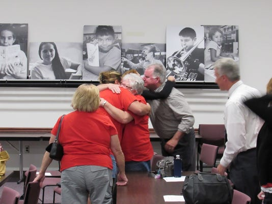 Members of Keep Us In Dover Schools (KIDS) embraces Wednesday morning in Harrisburg after the committee concludes its meeting in which it announced it would recommend to disapprove of Washington Township Independent School District's petition to transfer from Dover to Northern York school district.