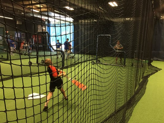 J.J. Gossard, 8, of Camp Hill, works on his stroke with his father Jason at the batting cages at Carmen Fusco's Baseball and Softball Academy in Fairview Township.