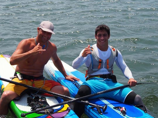 Second-place standup paddleboard finisher Sven Peltonen of Atlantic City, on left, congratulates Quintin Chiapperino, 19, of Saint Croix, U.S. Virgin Islands, on his win in the 22.5-mile Paddle For A Cause presented by J&L Amish Depot.