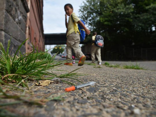 File photo of school-age children walking past a needle on the sidewalk of Governor Street on the way home from school.