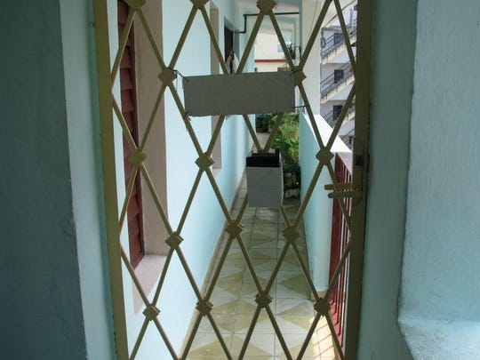 """A look through security bars that lead to hallway and porch outside apartment 208 37th Street, Vedado, Havana, Cuba, where fugitive Guillermo """"Willie"""" Morales now lives. For use with Mike Kelly sidebar to column on Joanne Chesimard. Photos by Mike Kelly / Staff"""