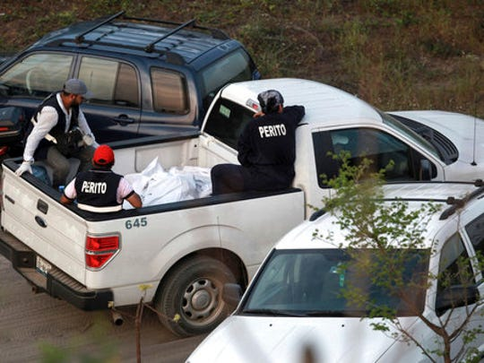 In this April 11, 2015 photo, special investigators guard bodies found in mass graves in a wooded area known as Colinas de Santa Fe on the outskirts of Veracruz, Mexico. Veracruz state's top prosecutor, Jorge Winckler, said the clandestine pits appeared to contain remains of cartel victims killed years ago.