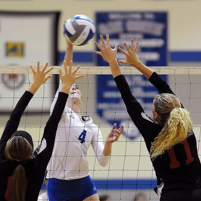 Oak Creek middle hitter Grace Paar, center hits the ball while being challenged by South Milwaukee blockers Laura Bolhuis, left and Haley Slusar during the WIAA regional semifinal girls volleyball match at Oak Creek High School Thursday, Oct. 20.