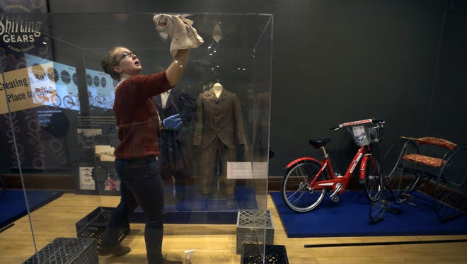 """Curator Emily Rock cleans the inside of a display case for the """"Shifting Gears"""" biking exhibit at the History Museum at the Castle in Appleton."""
