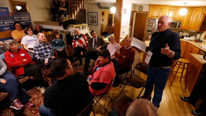 Caucus chairman Gary Weaver leads a living room full of caucusgoers through the process Feb. 1, 2016, at a home caucus site in Rippey, Iowa.
