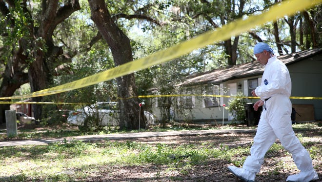 Leon County Sheriffs Office forensics experts gather evidence at a home in the 2600 block of Mission Road, the scene of a murder and one of the record number of homicides in the city of Tallahassee for 2017.