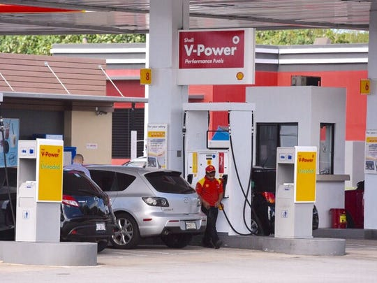 A gas attendant assists customers at the Shell station