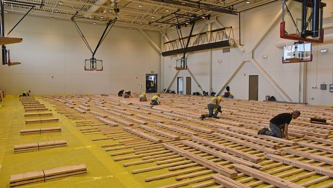 Workers lay the new gym floor at Foothills Activity Center on Jan. 11. The center's opening has been delayed for a second time.