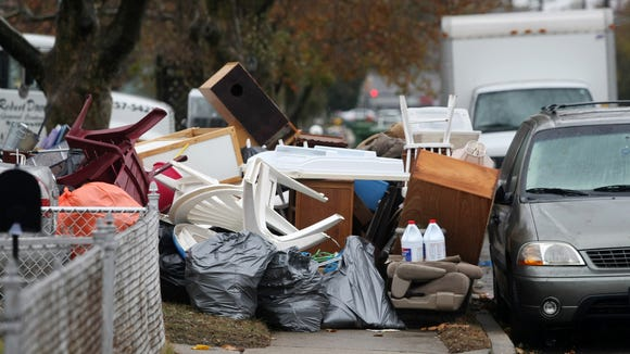 Flood debris is piled on the sidewalk along MacArhur Avenue, Wednesday, Nov. 7, 2012, in the wake of Superstorm Sandy.