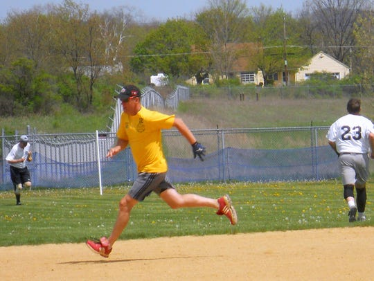 Players run the bases in a softball game during the