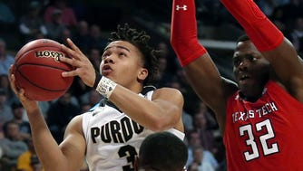 Purdue's Carsen Edwards drives to the basket between Texas Tech's Niem Stevenson, front, and Norense Odiase, right, during the first half of an NCAA men's college basketball tournament regional semifinal Friday, March 23, 2018, in Boston. (AP Photo/Mary Schwalm)
