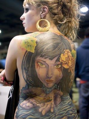 Jennifer Navar of Philadelphia displays her back tattoo at the Philadelphia Tattoo Arts Convention in 2012.
