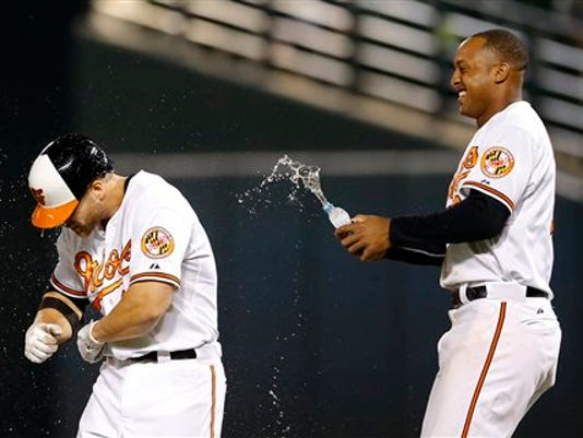 Baltimore's Jonathan Schoop, right, sprays water on teammate Chris Davis after Davis drove in the game-winning run on his single in the 13th inning against the Boston Red Sox on Tuesday in Baltimore. Baltimore won 6-5.