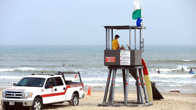 A lifeguard keeps watch as beach-goers enjoy the day during spring break Thursday, March 17, 2016, at South Packery Channel in Corpus Christi.
