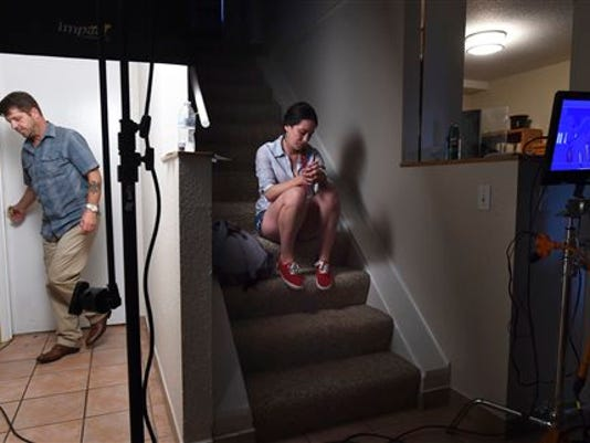 "In a Tuesday, July 21, 2015 photo, actors Jason Stange and Lisa van Dam-Bates wait outside a bedroom for their scenes during filming for the movie ""Marla Mae"" in Olympia, Wash. Stange was arrested on July 24, 2015, by federal agent for an outstanding probation warrant after being recognized in a photo in a Washington state newspaper that ran a story about the low-budget horror movie. Stange pleaded guilty to an armed bank robbery in 2006 and was given a 117-month prison sentence. A federal probation violation warrant was issued last year after Stange left a halfway house in Spokane. (Tony Overman, The Olympian via AP)"