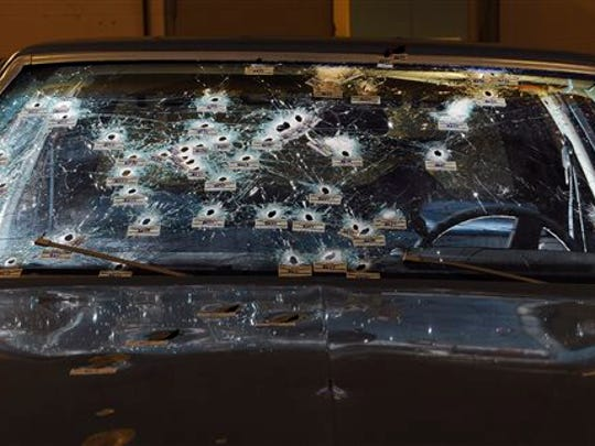 In this 2012 photo, bullet holes are visible on the windshield and hood of a Chevy Malibu peppered by gunshots after a high-speed chase that ended in the deaths of two unarmed suspects. Patrolman Michael Brelo faces two voluntary manslaughter charges in the shooting deaths of Timothy Russell and Malissa Williams.
