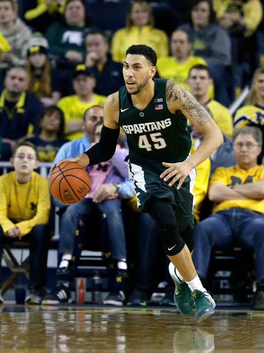 FILE - In this Feb. 6, 2016, file photo, Michigan State guard Denzel Valentine dribbles up court during the second half of an NCAA college basketball game against Michigan,  in Ann Arbor, Mich. The college basketball season is winding toward March Madness and a small group of players established themselves as front-runners to be the national player of the year. (AP Photo/Carlos Osorio, File)