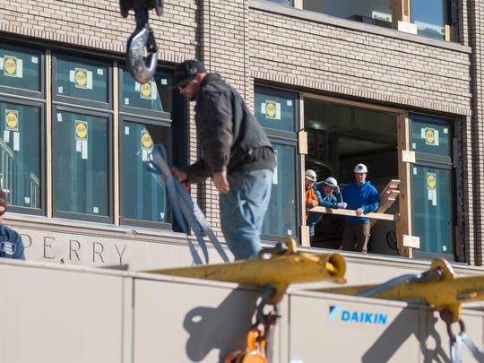 Workers watch from an open window area as the new air conditioning unit is readied to be hoisted on the roof  Monday, Oct. 10, outside the Sperry's MovieHouse in Port Huron.