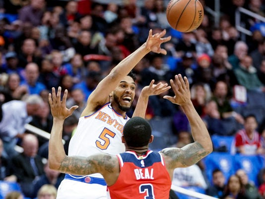 New York Knicks guard Courtney Lee (5) passes over Washington Wizards guard Bradley Beal (3) in the first half of an NBA basketball game, Sunday, March 25, 2018, in Washington. (AP Photo/Andrew Harnik)