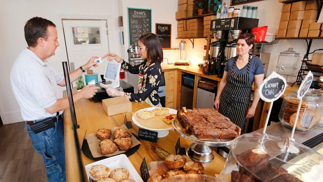 Owner Sarah Ray, right, looks on as Callum Amigleo rings up the purchase of Bruce Stewart Friday, October 6, 2017, at Sweet Revolution Bake Shop, 109 N. 5th Street in downtown Lafayette.