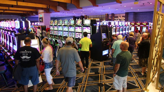 Patrons walk the Tiverton Casino floor on its opening day. The Town Council has scheduled a hearing for Aug. 5 to discuss a proposed ordinance that would restrict casino revenue to capital, debt service and infrastructure.