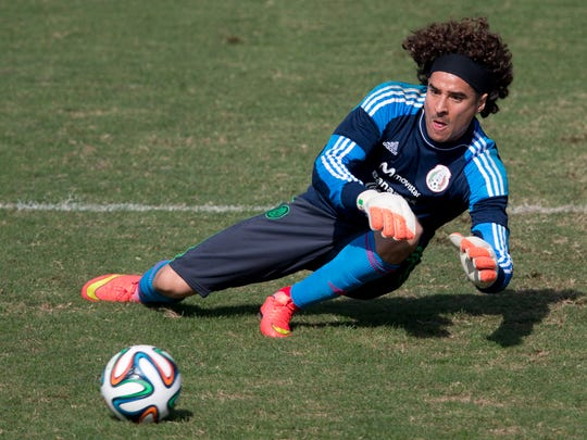 Mexico's star goalkeeper Guillermo Ochoa leaps to trap a ball during training Thursday. Mexico faces the high-powered Netherlands on Sunday.