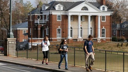 In this Nov. 24 file photo, University of Virginia students walk to campus past the Phi Kappa Psi fraternity house at the University of Virginia in Charlottesville, Va. Rolling Stone is casting doubt on the account it published of a young woman who says she was gang-raped at a Phi Kappa Psi fraternity party at the school, saying there now appear to be discrepancies in the student's account.