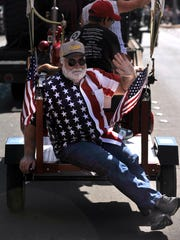 Don Henry waves from the back of a small trailer being pulled by a tractor during the West Texas Fair & Rodeo parade Sept. 9, 2017. Henry had been riding a scooter, but after it broke down in the middle of the parade route, he had to hitch a ride the rest of the way.