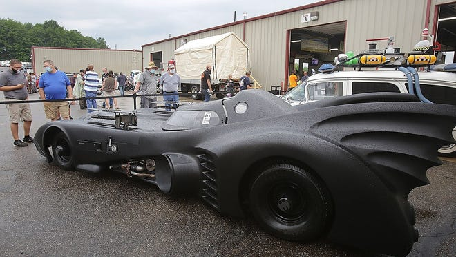 Auction attendees look over the replica movie vehicles at the Skipco Auto Auction Saturday.