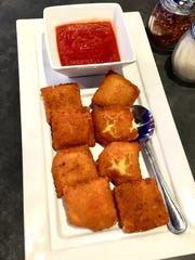 Off the appetizer menu, the fried ravioli ($7.99) are seasoned, lightly floured, egg-washed, breaded and deep-fried, and served with marinara sauce.