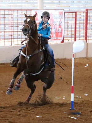 Jamie King of Huntsville, AL, rides in the U.S. Mounted Shooting event, Saturday, Oct. 31, at Kay Rodgers Park. Cowboy mounted shooting is a competitive equestrian sport involving the riding of a horse to negotiate a shooting pattern. Modern events use blank ammunition instead of live rounds, certified to break a target.