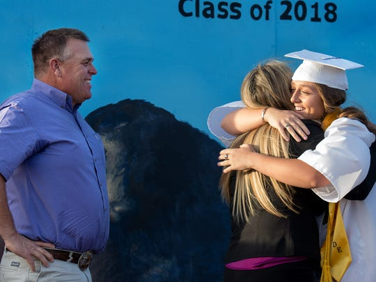 Valedictorian Emily Bobrick receives a congratulatory hug from her parents.