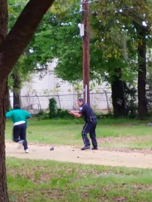 In this April 4, 2015, frame from video provided by Attorney L. Chris Stewart representing the family of Walter Lamer Scott, Scott appears to be running away from City Patrolman Michael Thomas Slager, right, in North Charleston, S.C. Slager was charged with murder Tuesday, hours after law enforcement officials viewed the dramatic video that appears to show Slager shooting a fleeing Scott several times in the back. (AP Photo/Courtesy of L. Chris Stewart)
