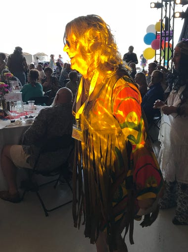 Patterns from the event lighting wash over Robin Boudreau at the Equality Celebration in St. George on May 19, 2018.
