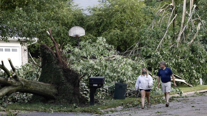 Natalie Lung, left, and her father, Mark Lung, walk on North Trainer Road heading home Monday after helping neighbors clean up storm damage in Rockford.