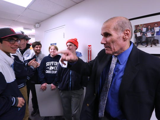 Suffern High School cross country coach Joe Biddy is greeted by his runners after a Suffern Central School District board of eduction meeting in Hillburn Feb. 6, 2018.