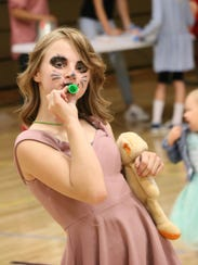 A carnival attendee sporting facepaint plays a kazoo