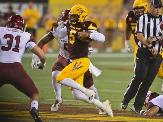 Arizona State Sun Devils quarterback Manny Wilkins (5) carries the ball as New Mexico State Aggies linebacker Dalton Herrington (31) defends during the first half at Sun Devil Stadium.