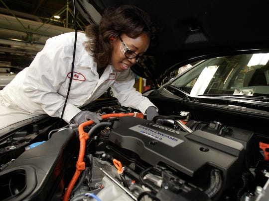 A worker inspects the hybrid engine of a 2014 Honda Accord Hybrid as production started at the plant in Marysville, Ohio, in September 2013.