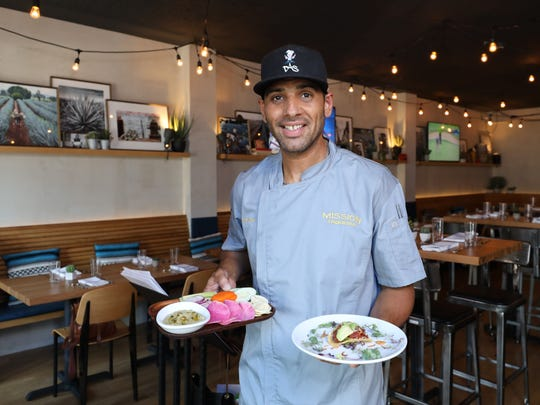 Chef David Santiago holds the pumpkin hummus and the