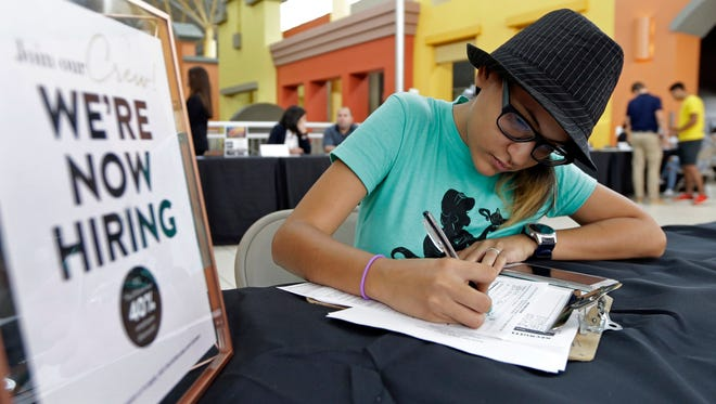 A job seeker fills out an application at a job fair.